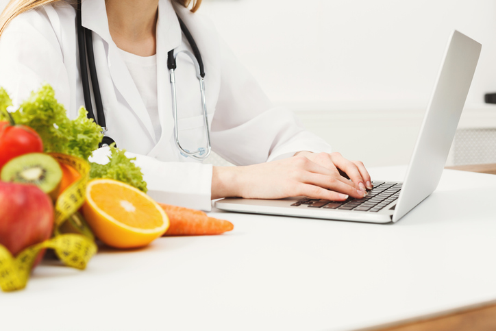 Female nutritionist working on laptop in office, close up. Hands of woman dietitian typing, counting calories or writing diet plan, copy space.